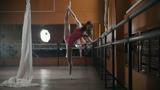 Pretty girl shows the flexibility of the body at the ballet bar