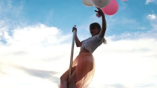 Pretty woman with bunch of balloons performs a pole-dance