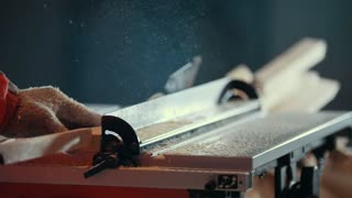Process of cutting wooden plank with dangerous circular electric saw, back view