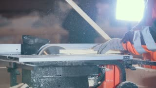 Process of cutting wooden plank with dangerous circular electric saw, profile view