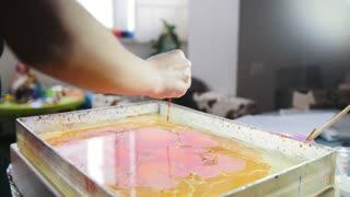 Process of painting - purple paint drops on yellow background - woman draws on water in Liquid Ebru art technics