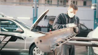 Process of repairing the vehicle - worker polishing detail of the car