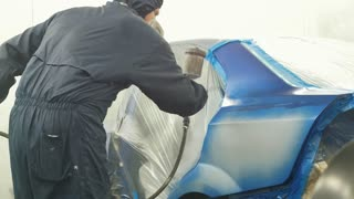 Professional car painter in vehicle workshop