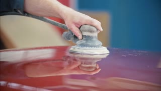 Professional car service - a worker polishes red automobile