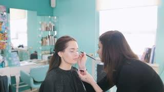 Professional makeup artist doing make-up with eye shadows