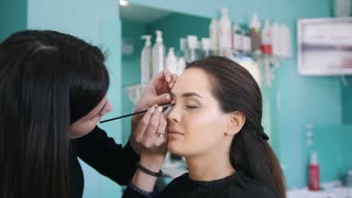 Professional visage artist doing make-up with black eyeliner for beautiful woman