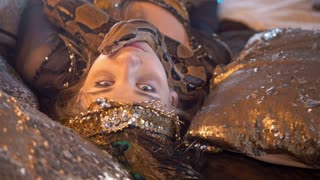 Python crawling on the face of young female dancer in bright costume