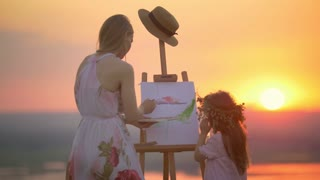 Rear view of mother and daughter together draws landscape on the hill at sunset