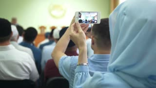 Rear view of muslim people at the islamic conference - women in hijab shooting on smartphone