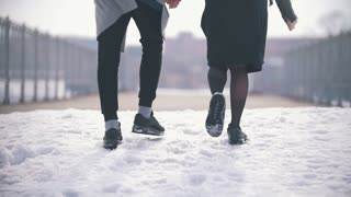 Rear view of young couple walking hand in hand