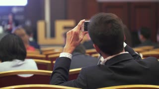 Rear view of young man takes picture of awards ceremony