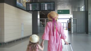 Rear view of young mother and cute daughter holding hands at the airport and watching flight schedule