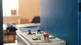 Red button on folding machine - printing polygraph industry, close up
