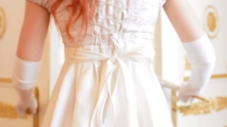 Red-haired girl in a vintage ball dress entered in the ballroom