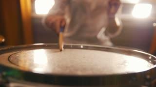 Repetition. Ginger girl plays drums tom-tom . Portrait. Backlights.
