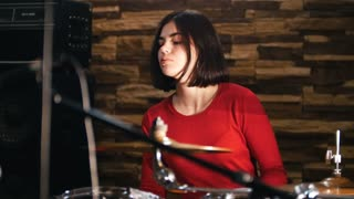 Repetition. Girl actively plays the drums