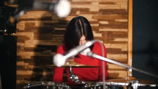 Repetition. Girl fervently plays the drums