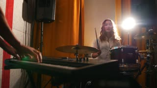 Repetition. Girl playing drums and a guy on keyboards. Girl and drums in focus