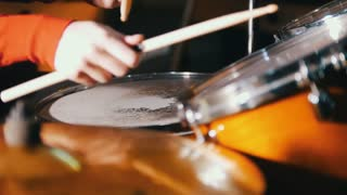 Repetition. Girl playing drums in the studio. Only hands shown