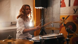 Repetition. Redhead girl plays on drums. Studiolights