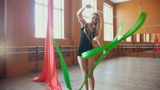 Rhythmic gymnastics - young woman training a gymnastics exercise with a ribbon, slow-motion