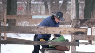 Rider on the farm prepares the saddle before the riding