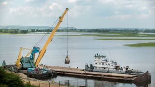 River cargo crane - process of loading sand from the barge to the ship, time-lapse