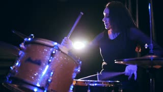 Rock girl percussion drummer performing with drums, slow motion
