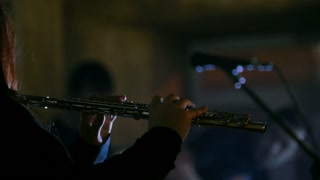 Rock scene - young woman playing the flute at concert in bar