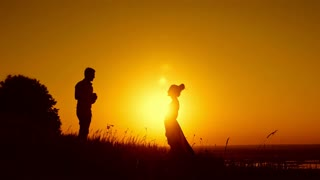 Romantic Silhouette of Man Getting Down on his Knee and Proposing to Woman on summer meadow - Couple Gets Engaged at Sunset - Man Putting Ring on Girl's Finger