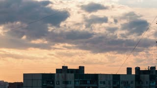 Roof of the old panel houses in big city in cloudy sky at sunset