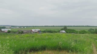 Rural russian landscape - old village with wooden houses and orthodox church - panoramic