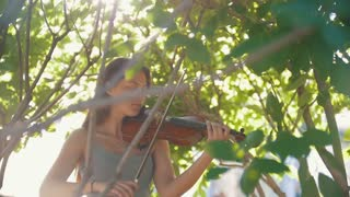 Sad female musician playing a violin among the tree branches at sunset