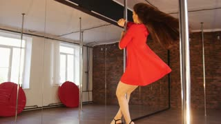 Sexy girl in red dress pole dance. Spinning around the pole