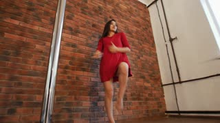 Sexy girl in red dress training pole dancing. Jumping on the pole