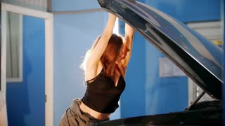 Sexy mechanic girl leans on an open car hood and closes it