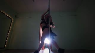 Sexy woman with black long hair spinning on a pole in a studio