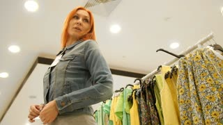 Shopping for women - girl chooses a jeans jacket