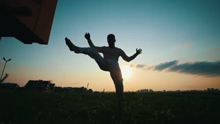 Silhouette of a man dancing capoeira at sunset, summer evening