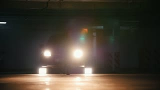 Silhouette of a young stylish guy freerunner doing a series of jumps, flips, and turns in the garage in front of car's headlights - slow-motion