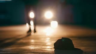 Silhouette of male walking in garage and lifts up the hat in front of headlights - feet close up