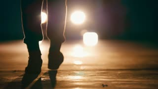 Silhouette of man in garage in front of headlights -feet close up