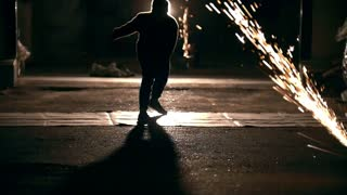 Silhouette of man performing acrobatic elements through the sparks from grinder