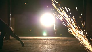 Silhouette of man performing martial elements through the sparks from grinder at night