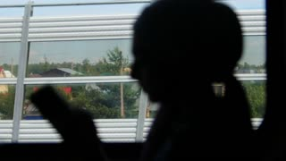 Silhouette of muslim women looking at the phone, during train journey