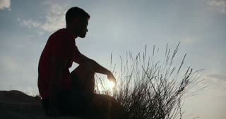 Silhouette of young man sitting on the edge of a cliff and looking at the sunset