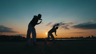 Silhouettes of two sporting men, who dance the Brazilian capoeira on the background of summer sunset