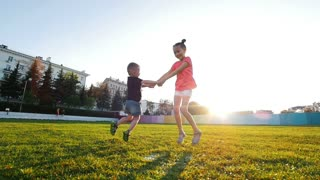 Sister and brother hold hands and cheerfully jump on the grass with puddles. Flying spray, children laugh.