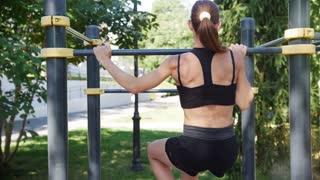 Skinny sporty girl doing exercises on the bar