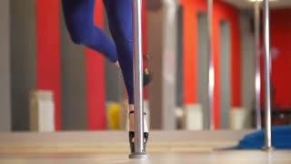 Slim female legs in black high-heeled shoes dancing on a pole dance
